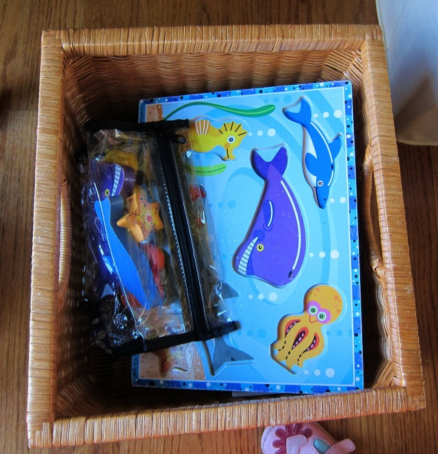 Puzzles are in a basket with the pieces to each kept in a clear cosmetic bag with a zipper.